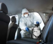 man-wearing-personal-protective-equipment-and-spraying-inside-car