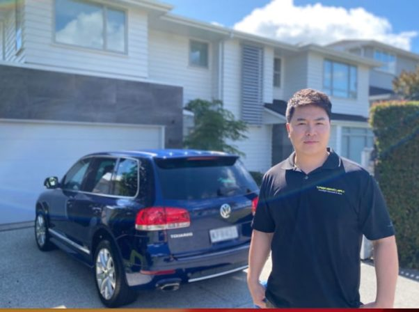 renewcar-owner-with-black-car-and-house-at-the-back